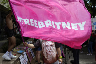 """A Britney Spears supporter waves a """"Free Britney"""" flag outside a court hearing concerning the pop singer's conservatorship."""