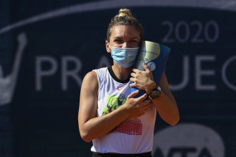 Simona Halep celebrates with the Prague Open trophy after victory in her first tournament since the coronavirus shutdown. She will not travel to the US but stay in Europe.