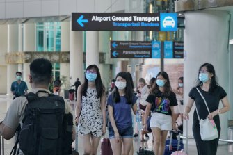 Passengers wear masks in the arrival hall of Bali's Denpasar airport.