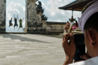 Tourists pose at Lempuyang Temple, also known as the Gates of Heaven.