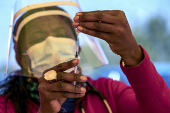 A health worker prepares a dose of the Pfizer vaccine at the Orange Farm Clinic near Johannesburg in South Africa.