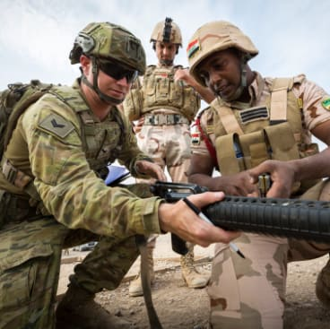 Australian Army soldier Corporal Eamon Baldwin helps an Iraqi Army soldier adjust his sights during a shooting competition at Taji Military Complex, Iraq.