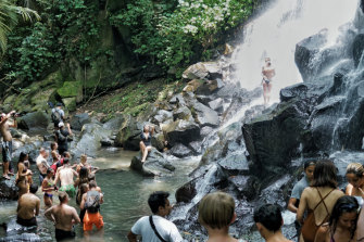 Tourists line up while others pose under the Kato Lampo waterfall in Gianyar, Bali.