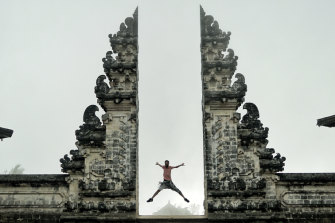 A tourist poses at the Lempuyang Temple in Bali.