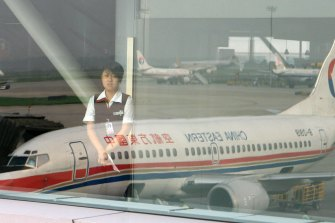 A ground staff is seen through a window on which the image of a China Eastern airplane in Beijing.
