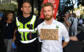 Victoria Police arrest a protester who glued his hand to a window during a protest at Siemens.