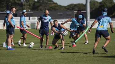Tom Staniforth passes a ball as Waratahs players go through their paces at training in Sydney.