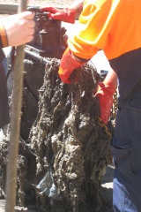 Sydney Water staff manually removing a blockage of wet wipes.