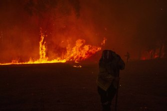Firefighters undertake property protection as a bushfire impacts property in Mangrove Mountain on December 5.