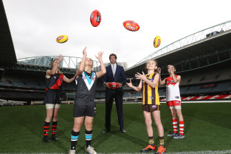 AFL chief Gillon Mclachlan poses with young footballers Nora Don, Fadilla Taleb, Leni Burgoyne and Layla Rabah.