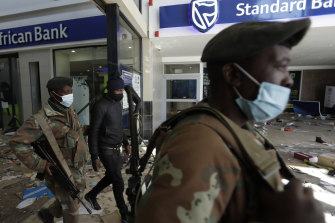 Soldiers escort a man suspected of looting from inside a trashed shopping mall in Soweto, near Johannesburg.