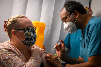Dr Mukesh Haikerwal administers a Pfizer to a patient at his Altona North clinic.
