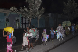 People flee with their belongings after the eruption of Mount Nyiragongo, in Goma, Congo.