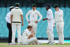 All-rounder Cameron Green goes down after being struck in the head while bowling at the SCG on Friday.