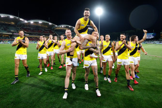 Trent Cotchin is chaired from the field by teammates Dylan Grimes (left) and Dustin Martin (right) after his 250th match in Richmond's preliminary final win over Port Adelaide.