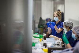 Staff prepare vaccine doses at the Melbourne Convention and Exhibition Centre.