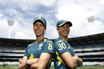 Erin Burns and Delissa Kimmince pose at training on Saturday, their shirts bearing the names of injured teammates Ellyse Perry and Tayla Vlaeminck.