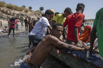 Tigray refugees who fled the conflict in the Ethiopia's Tigray ride a boat on the banks of the Tekeze River on the Sudan-Ethiopia border.