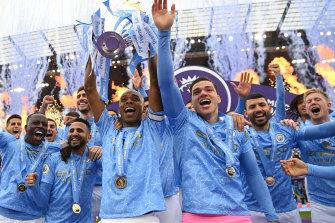 Fernandinho lifts the trophy for Manchester City.