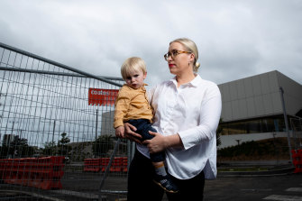 Zetland resident Angela Winkler and her two-year-old son Alfred in front of the fenced-off aquatic centre in Green Square.