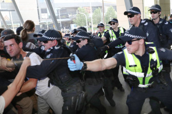 Police use pepper spray as protesters attempt to stop conference members entering the conference on Wednesday morning.