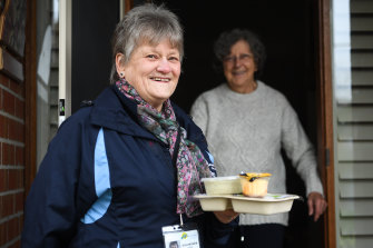 Adele Allen delivers a meal to Patricia Shing on Friday. She started doing deliveries for Meals on Wheels 50 years ago.