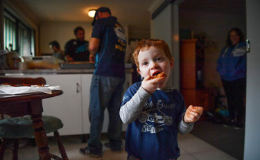 Jett Napoli, 3, taste tests some meatballs while family and friends make salami.