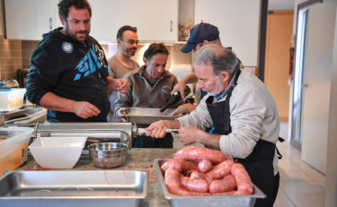 Joe Napoli, right, guides meat into the casings from the compressing machine while family friend Michael Cini, left, looks on.