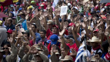 """Supporters of Venezuelan President Nicolas Maduro raise their hands swearing allegiance to the fatherland during an """"anti-intervention"""" march this week."""