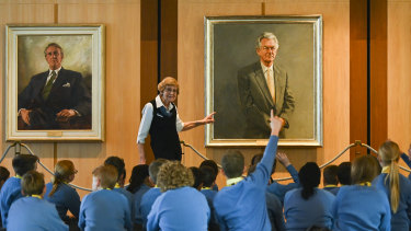 School children listen to a tour guide in front of the official portrait of the late PM Bob Hawke at Parliament House in Canberra.