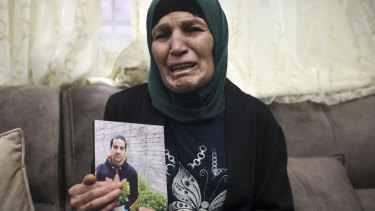 Rana, mother of Iyad Halak, 32, holds his photo at their home in East Jerusalem's Wadi Joz.