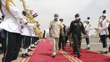 President of the Sudanese Transitional Council General Abdel Fattah al-Burhan, right, and Eritrean President Isaias Afwerki inspect a guard of honour at the Khartoum airport in Khartoum.