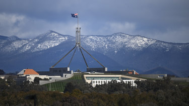 House of pain: Parliament House is seen in front of snow-covered hills surrounding the Australian Capital Territory.