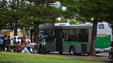 Rough sleepers wait to  board a Transperth bus that will take them to temporary accommodation.