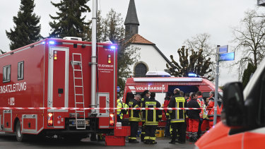 Police and rescue workers stand next to the scene of a car crash at the carnival parade in Volkmarsen, central Germany.