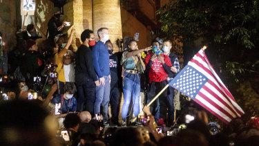 Black Lives Matter organiser Teal Lindseth addresses protesters as Portland mayor Ted Wheeler, left, listens in July.