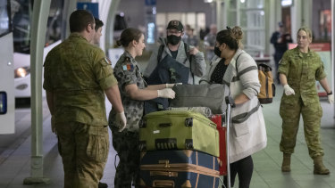 Passengers from San Francisco arrive at Sydney International Airport before being transported to hotel quarantine on Wednesday evening.