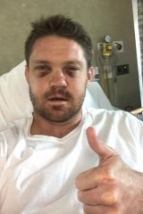 Black and blue: Chris Lawrence in his hospital bed in New Zealand.
