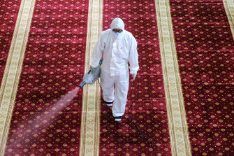 A worker wearing a protective suit and a mask sprays disinfectant at a mosque near Kuala Lumpur, Malaysia.