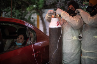 Volunteers treat patients suffering from Covid-19 with free oxygen at a makeshift clinic in a parking lot outside the Gurdwara Damdama Sahib on May 03, 2021 in New Delhi, India.