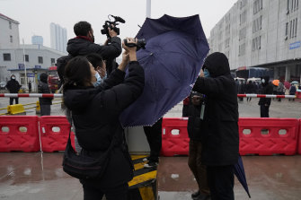 A plainclothes security person uses his umbrella to block journalists from filming after the World Health Organisation team arrive at the Baishazhou wholesale market on the third day of field visit in Wuhan in central China's Hubei province on Sunday, January 31.