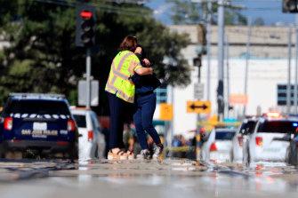 Two people hug in the street near the rail yard where nine people were shot dead in San Jose.