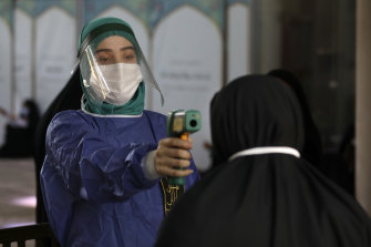 A volunteer checks the temperature of a worshipper as she enters the mosque of Tehran University.