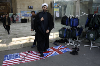 A cleric walks on the US and British flags while leaving a gathering to commemorate the late Iranian General Qassem Soleimani, who was killed in a US drone attack on January 3.