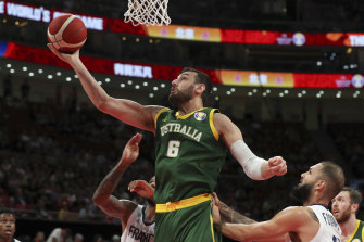 Andrew Bogut of Australia puts up a shot over Amath M'Baye, left, and Evan Fournier of France during their third placing match for the FIBA Basketball World Cup.