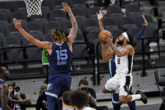 Spurs guard Patty Mills, right, takes his shot.