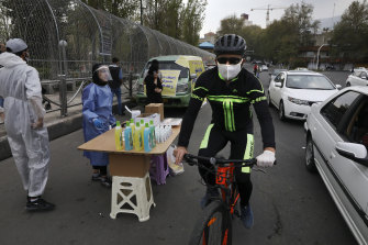 A cyclist rides past a group of people selling hand sanitiser in Tajrish square in northern Tehran, Iran.