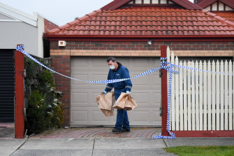 Forensic officers remove evidence from the Mill Park home on Wednesday morning.