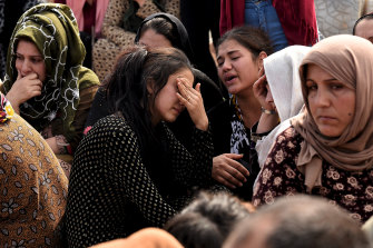 Relatives grieve for teenage soldier Adnan Hassan. It took his family four days to retrieve his body from the rubble.