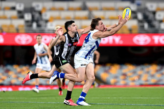 Collingwood and North Melbourne do battle under lights at the Gabba.